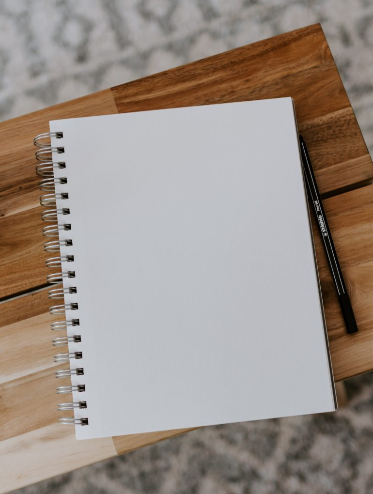 notebook on wood table with coffee